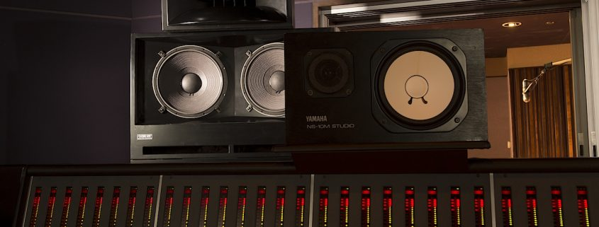 Speaker Placement - how to place your studio monitors screen shows a pair of speakers on a mixing console